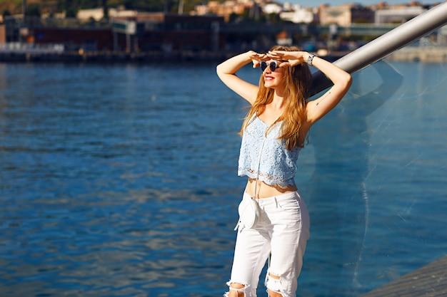 官能的な金髪の女性、トレンディな夏の服装、パステルカラーのロマンチックな海の景色の肖像画、一人旅、休暇、白いデニム、サングラス。