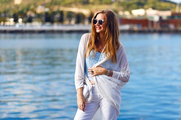 Romantico ritratto vista mare di sensuale donna bionda, vestito estivo alla moda, colori pastello, viaggio da solo, vacanza, denim bianco, occhiali da sole.