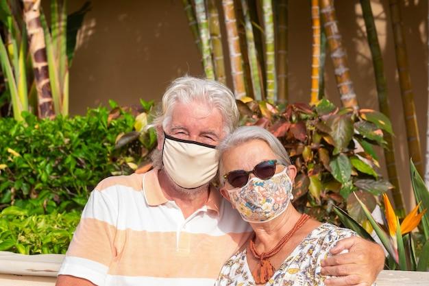 코로나바이러스로 인해 얼굴 마스크를 쓰고 열대 정원에서 포옹하는 낭만적인 노부부 - 여름 휴가에 은퇴한 두 사람을 위한 편안한 생활 방식