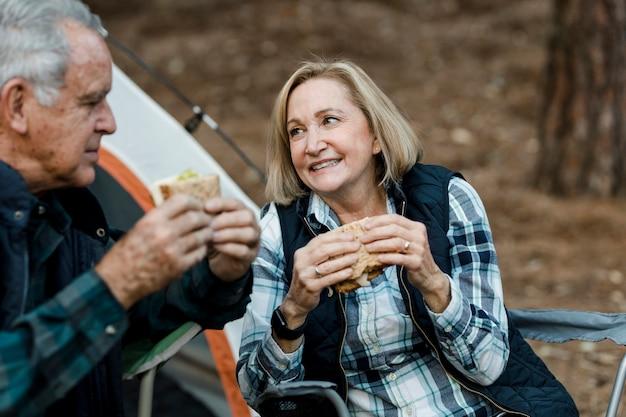 キャンプ場でピクニックをしているロマンチックな年配のカップル