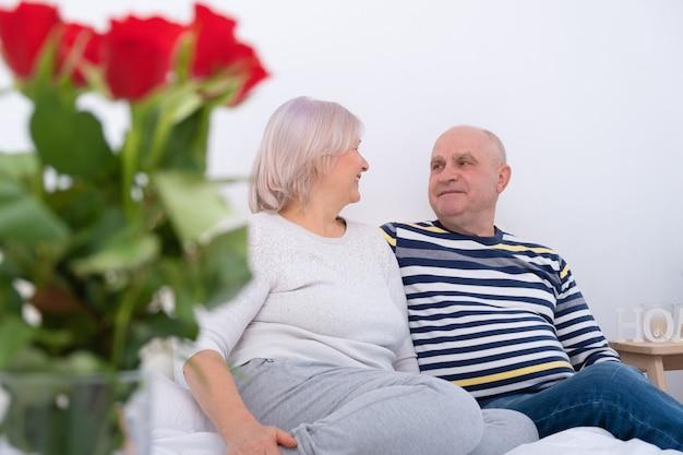 Романтическая пара старших обниматься, сидя на кровати. букет роз.