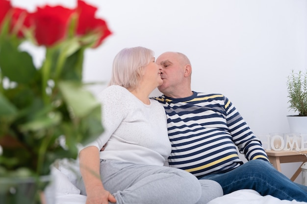 Романтическая пара старших целоваться на кровати. букет роз.