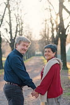 Romantic senior couple portrait walking outdoors hands together in the park.