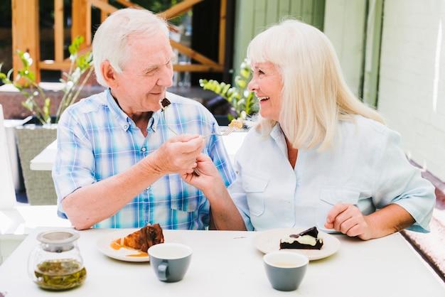 Romantic senior couple sitting in cafe on terrace and enjoying cakes