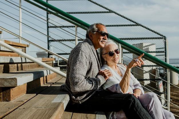 桟橋に座っているロマンチックな年配のカップル