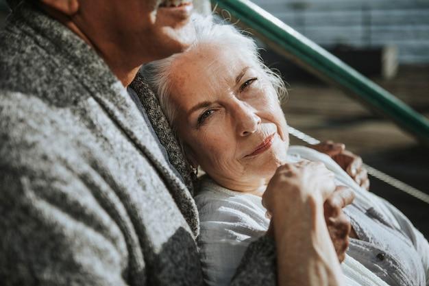 Романтическая пара старших, сидя на пирсе