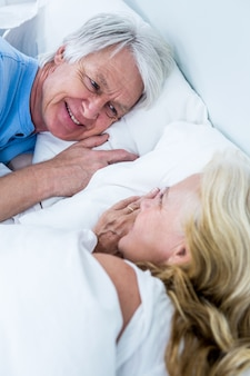 Romantic senior couple sleeping on bed