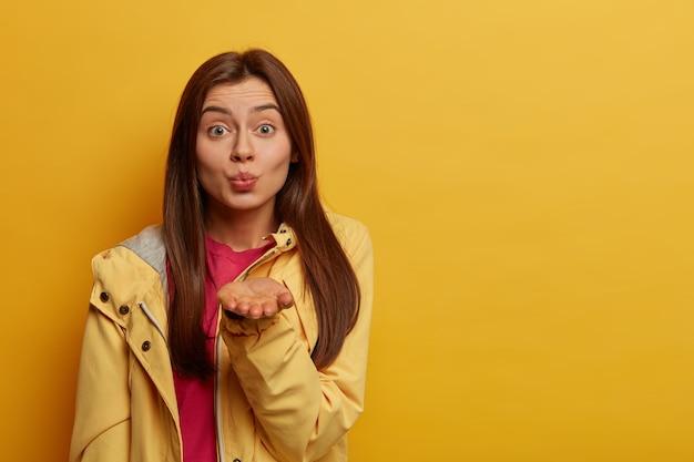 낭만적 인 관능적 인 여자는 입술을 둥글게 유지하고, 카메라에 공기 키스를 불고, 애정을 표현하고, 부드러운 외모를 가지고, 노란색 아노락을 입고, 실내에 서서 공간 영역을 복사합니다. 사람들