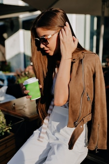 一杯のコーヒーが髪に触れているロマンチックな官能的な女性は、街で楽しい時間を過ごします。