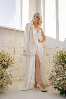 재킷과 긴 흰색 드레스를 입은 로맨틱한 섹시한 여성이 카모마일 꽃으로 창가에 서 있습니다. 완벽한 몸매의 금발 소녀
