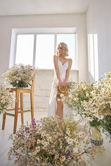 長い白いウェディング ドレスを着たロマンチックなセクシーな女性は、カモミールの花で窓の近くに立っています。完璧な体型のブロンドの女の子