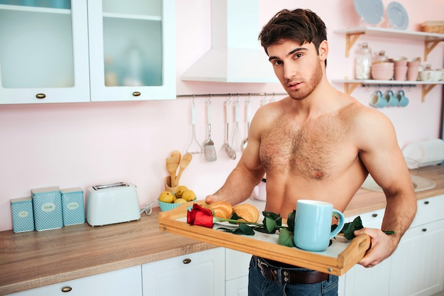 Romantic sexy young man hold tray with flower and breakfast on it. guy look  and pose.