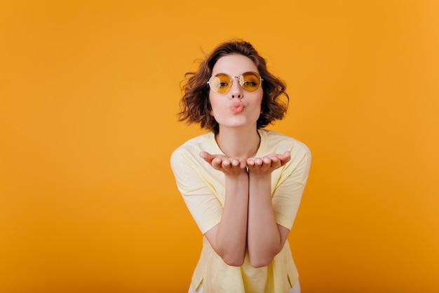 Romantica donna dai capelli corti in occhiali vintage in posa con l'espressione del viso incantevole. ragazza allegra in maglietta gialla che invia bacio dell'aria durante il servizio fotografico.