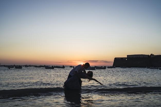 석양에 캡처 한 해변에서 커플의 실루엣의 로맨틱 샷
