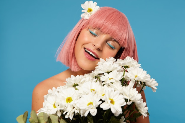 Romantic shot of young attractive pink haired female with colored makeup smiling pleasantly with closed eyes while posing in white camomiles