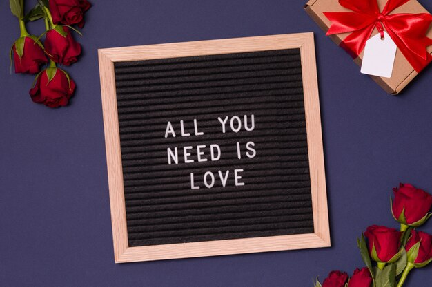 Romantic sign on letter board on valentines day background with red roses and gift.
