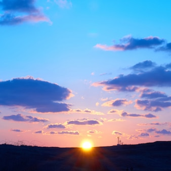 Романтическое небо с солнцем, красивые синие, красные и желтые облака