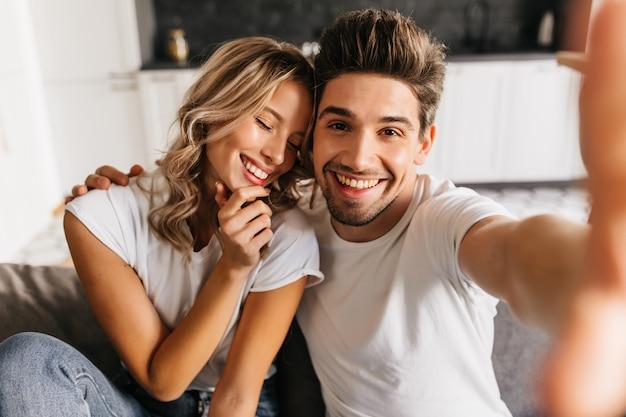 Coppie sorridenti romantiche che fanno selfie a casa seduto sul divano. l'uomo e la sua ragazza sorridono felicemente con gli occhi chiusi.