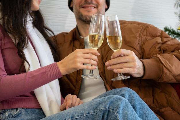 소파에 앉아 거실에서 샴페인 잔을 부딪 치는 낭만적 인 웃는 연인. 크리스마스, 새해 및 사랑 개념