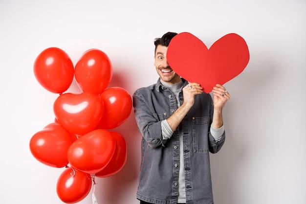 ロマンチックな笑顔の男はバレンタインハートカードで顔を覆い、カメラを見て幸せそうに見え、パートナーとの恋人の日を祝い、白の上に立っています。