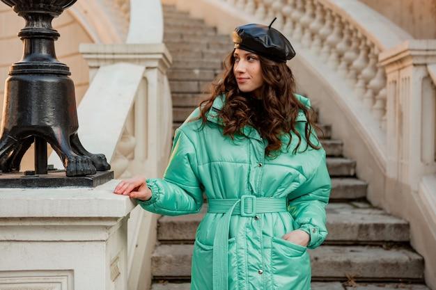 冬の秋のファッショントレンドの青いフグコートと古い美しい通りの階段で帽子ベレー帽でポーズをとってロマンチックな笑顔のスタイリッシュな女性