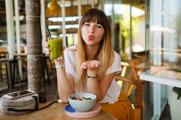 Romantic smiling woman send kiss and eating healthy vegan breakfast.