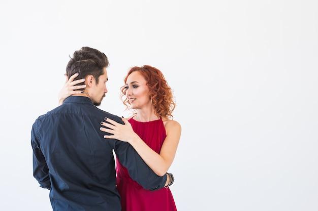ロマンチックな社交ダンス、人々のコンセプト-スタジオでバチャタを踊るカップル、後ろから女性を抱き締める男性。コピースペースのある壁