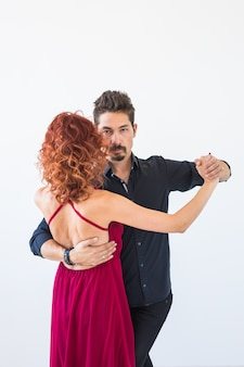 Romantic, social dance, people concept - couple dancing the salsa or kizomba or tango on white