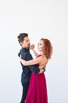 ロマンチックな社交ダンス、人々のコンセプト-白い壁にサルサ、キゾンバ、タンゴを踊るカップル。