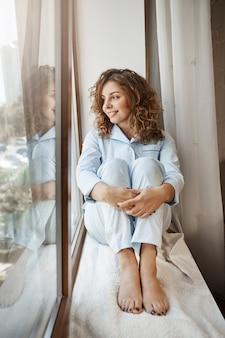 Романтическая душа мечтает найти страстную половинку. портрет привлекательной уютной европейской девушки сидя на подоконнике в пижаме, глядя через окно с улыбкой, думая или имея идею