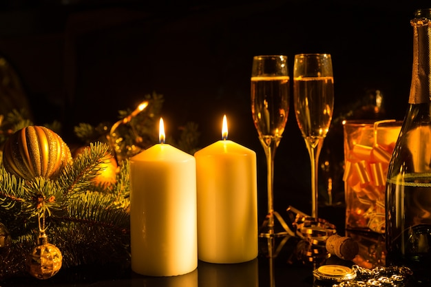 クリスマスの装飾とギフトで暗い背景にシャンパンのガラスを照らす点灯キャンドルのロマンチックな静物-暖かい光の中でお祝いの燃えるキャンドルの感傷的なイメージ