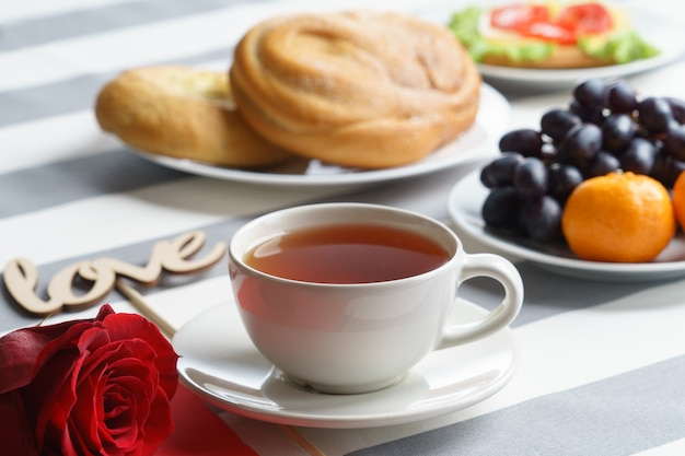 Романтический натюрморт с чашкой чая и ярко-красными праздничными атрибутами. Premium Фотографии