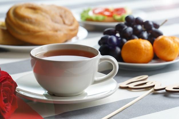 Романтический натюрморт с чашкой чая и ярко-красными праздничными атрибутами.