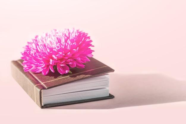 시와 아름다운 분홍색 꽃이 있는 미니북이 있는 낭만적인 정물. 빈티지와 레트로 스타일. 시와 문학 개념입니다.