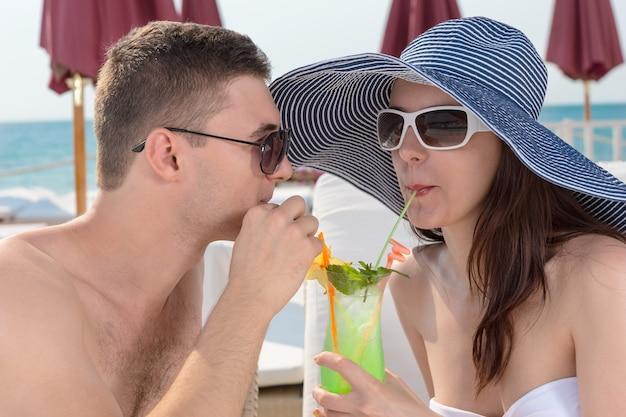 彼らは高級海辺のリゾート、クローズアップビューで彼らの新婚旅行を祝うときに2つのストローからすすりながらトロピカルカクテルを共有するロマンチックでスタイリッシュな若いカップル