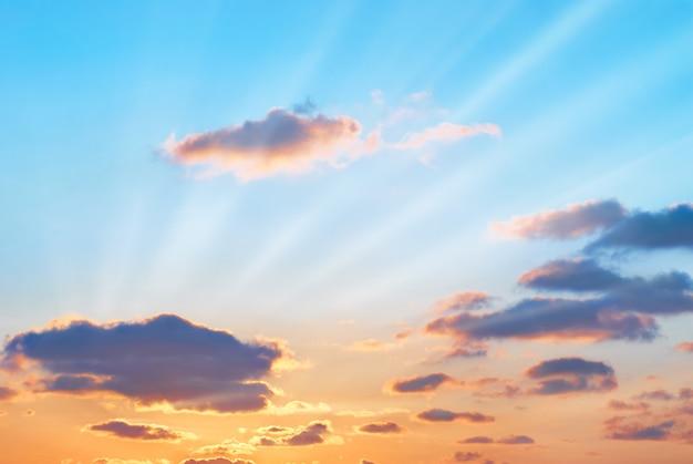 Романтический закат с красивыми синими, красными и желтыми облаками и солнечными лучами