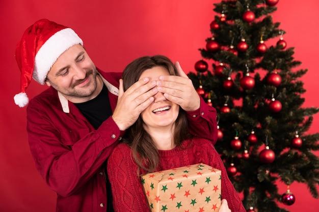 Романтический сюрприз на рождество, красивая женщина получает подарок от своего парня, мужчина закрывает девушке глаза руками.