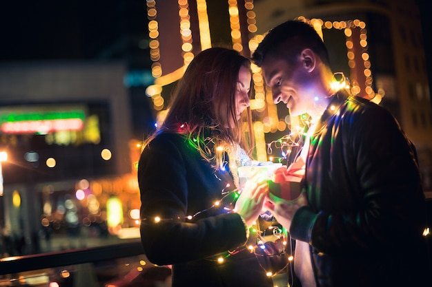 クリスマスのロマンチックな驚き、女性は彼女のボーイフレンドから贈り物を受け取ります