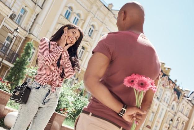 Романтический сюрприз молодая разнообразная пара, стоящая на городской улице, парень держит букет