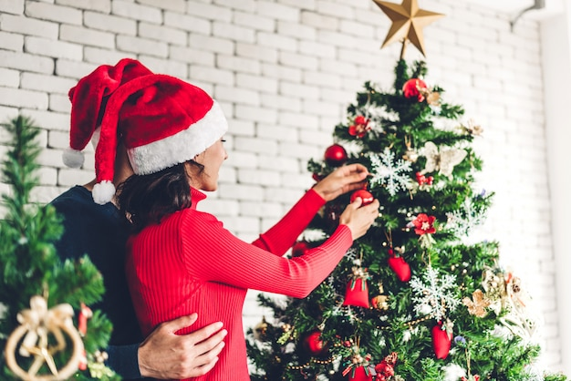 Romantic sweet couple in santa hats having fun decorating christmas tree and smiling while celebrating new year eve