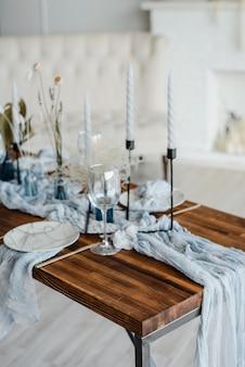 休日の夕食のためのロマンチックなテーブルセッティング、ドライフラワー、プレート、黄金のカトラリー、白いカンデール、明るいほこりっぽい青いランナーを添えた木製のテーブル。セレクティブフォーカス。