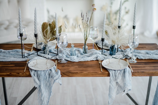 Romantic table setting for holiday dinner, wooden table served with dried flower, plates, golden cutlery, white candeles, bright dusty blue runner. selective focus.