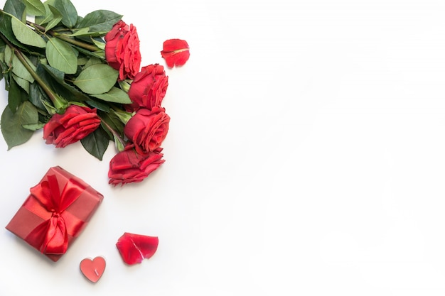 Romantic table setting with bouquet of red roses and gift. view from above. valentine day.