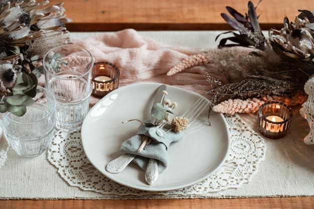 Романтическая сервировка стола с зажженными свечами и засушенными цветами на свадьбу или день святого валентина.