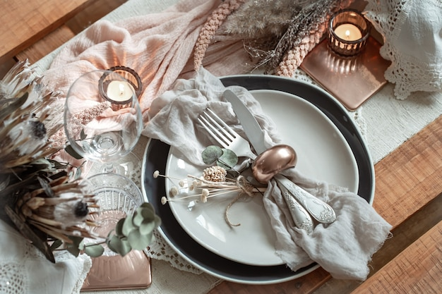Romantic table setting with burning candles and dried flowers for the wedding with many decorative details