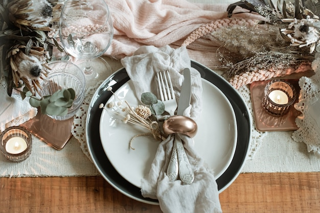 Romantic table setting with burning candles and dried flowers for the wedding with many decorative details.