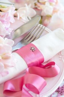 フリージアの花とピンクのリボンでロマンチックなテーブルセッティングをクローズアップ