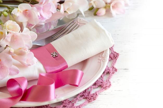 白い木製のテーブルのフリージアの花とロマンチックなテーブルセッティングはコピースペースでクローズアップ