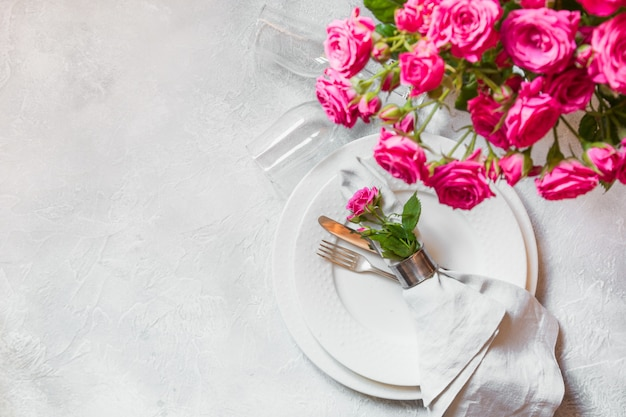 Romantic table setting with pink roses as decor, dishware, silverware, and decorations. top view.