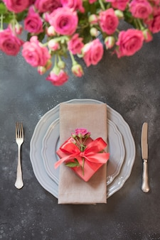 Romantic table setting with pink roses, vintage dishware, silverware.